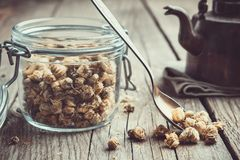 Glass jar of dry healthy chamomile buds, spoon and vintage teapot on old n wooden table. stock photo