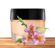 Glass jar of face cream and lilly flower on wooden table Stock Photo