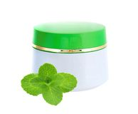 Glass jar of face cream with mint leaves Royalty Free Stock Photos