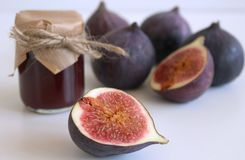 Glass jar of fig jam and fresh figs on white wooden table, side view. Close-up. Food concept Stock Image