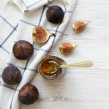 Glass jar of fig jam and fresh figs on white wooden table, top view. Flat lay, overhead, from above. stock images