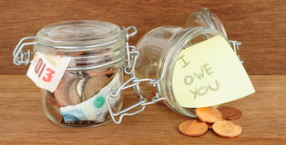 Glass Jar Filled With Cash. Glass jars filled with cash savings on a wood background Royalty Free Stock Images