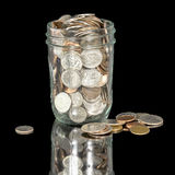 Glass jar filled with coins with reflection Stock Photography