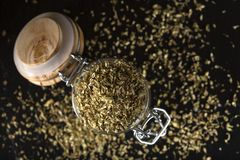 Glass jar filled with dried oregano on dark slate background Royalty Free Stock Image