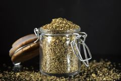 Glass jar filled with dried oregano on dark slate Stock Photo