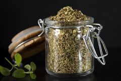 Glass jar filled with dried oregano over dark slate Stock Images