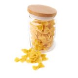 Glass jar filled with dry farfalle pasta over isolated white background Royalty Free Stock Photo