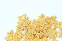 Glass jar filled with dry farfalle yellow pasta over isolated white background royalty free stock photos
