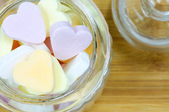 Glass jar filled with heart candies. Glass jar filled with colorful heard candies on a wooden surface Stock Photo