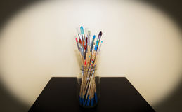 Glass jar filled with paint stained paintbrushes Stock Image