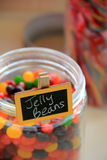 Glass jar of flavorful jelly beans. And other candies on table Stock Photo