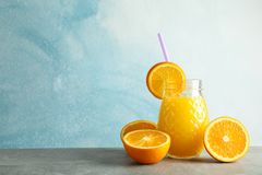 Glass jar with fresh orange juice, tubule and oranges on grey table against color background, space for text. Fresh natural drink stock image