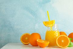 Glass jar with fresh orange juice and tubule, oranges on white table against color background, space for text. Fresh natural drink royalty free stock image
