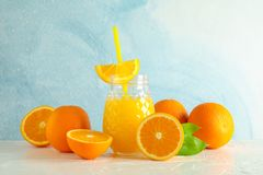 Glass jar with fresh orange juice and tubule, oranges on white table against color background. Space for text. Fresh natural drink stock images