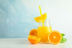 Glass jar with fresh orange juice and tubule, oranges on white table against color background, space for text. Fresh natural drink stock image