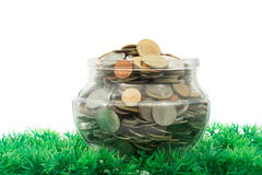Glass jar full of bath coins on artificial grass Stock Photography