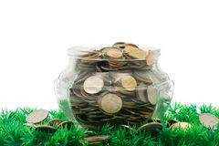 Glass jar full of bath coins on artificial grass Royalty Free Stock Images