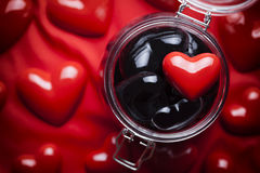 Glass jar full of black hearts and red heart on top Royalty Free Stock Image