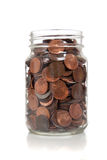 Glass jar full of coins. A glass jar full of coins including pennies, nickels, dimes and quarters stock photo