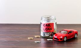 Glass jar full of coins - car loan. A glass jar full of coins and a plant growing through it. Concept image showing Car loan royalty free stock images