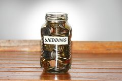A glass jar full of coins to represents wedding concept. With masking tape and wedding written on it Royalty Free Stock Image