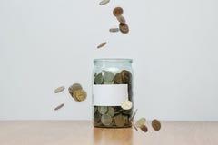 Glass jar full of falling coins, blank sticker, money box. Cash or penny saving Stock Photo