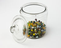 Glass jar half full of colorful glass marbles Royalty Free Stock Photos