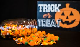 Halloween Fun. A glass jar has tumbled and spilled some of its candy corn on a table stock image