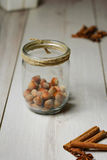 Glass jar with hazelnuts. On a wooden background, cinnamon and Badea Royalty Free Stock Photo
