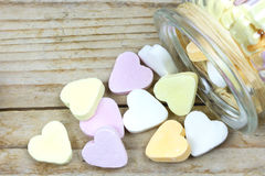 Glass jar with heart candies fallen out. On a wooden surface Stock Images