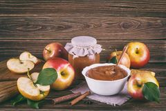 Glass jar of homemade apple jam with fresh fruits and ingredients. On woody background Stock Images