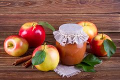 Glass jar of homemade apple jam with fresh fruits and ingredients. On woody background Royalty Free Stock Photo