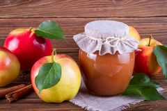 Glass jar of homemade apple jam with fresh fruits and ingredients. On woody background Stock Image