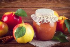 Glass jar of homemade apple jam with fresh fruits and ingredients. On woody background Royalty Free Stock Images