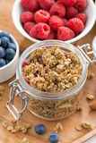 Glass jar with homemade granola and fresh berries, top view. Vertical Stock Photography