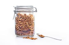 Glass jar of homemade granola with spoon. A glass jar of homemade sugar free granola with spoon Royalty Free Stock Photography