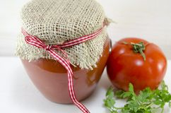 Glass jar of homemade ketchup and a tomato Stock Images