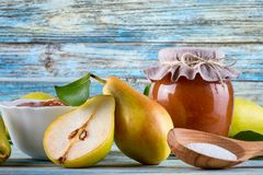 Glass jar of homemade pear jam with fresh fruits and ingredients. On woody background Royalty Free Stock Photography