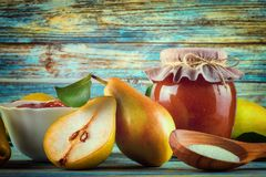 Glass jar of homemade pear jam with fresh fruits and ingredients. On woody background Stock Photography