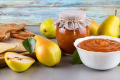 Glass jar of homemade pear jam with fresh fruits and ingredients. On woody background Stock Image