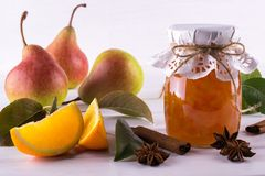 Glass jar of homemade pear and orange  jam with fresh fruits  on the table Royalty Free Stock Photo