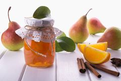Glass jar of homemade pear and orange  jam with fresh fruits  on the table. Glass jar of homemade pear and orange  jam with fresh fruits  on the white table Stock Photo