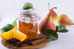 Glass jar of homemade pear and orange  jam with fresh fruits  on the table. Glass jar of homemade pear and orange  jam with fresh fruits  on the white table Stock Image
