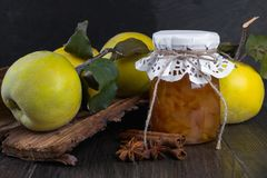 Glass jar of homemade quince  jam with fresh fruits. On the table Royalty Free Stock Photos