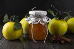 Glass jar of homemade quince  jam with fresh fruits. On the table Royalty Free Stock Photography
