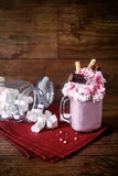 Glass jar of homemade raspberry smoothie cocktail, served with whipped cream, caramel jelly beans and wafer rolls over Stock Images