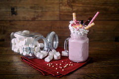 Glass jar of homemade raspberry smoothie cocktail, served with whipped cream, caramel jelly beans and wafer rolls over Stock Photos