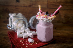 Glass jar of homemade raspberry smoothie cocktail, served with whipped cream, caramel jelly beans and wafer rolls over Royalty Free Stock Photography