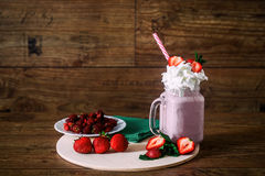 Glass jar of homemade strawberry smoothie cocktail, served with whipped cream, green mint and fresh berries over old Stock Photo