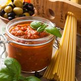 Glass jar with homemade tomato pasta sauce. Glass jar with homemade classic spicy tomato pasta or pizza sauce with olives and basil. Italian helthy food Royalty Free Stock Photo